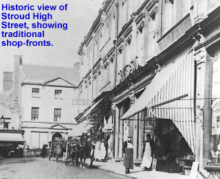 Historic view of Stroud High Street, showing traditional shop-fronts.