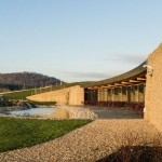 Gloucester Services - back - drystone wall, terrace, pond, cascade, grass roof, hills. Photo by Paul Miller