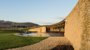 Gloucester Services  - back - drystone wall, terrace,  pond, cascade, grass roof, hills. Photo by Paul Miller on behalf of Glenn Howells Architects. Click to enlarge